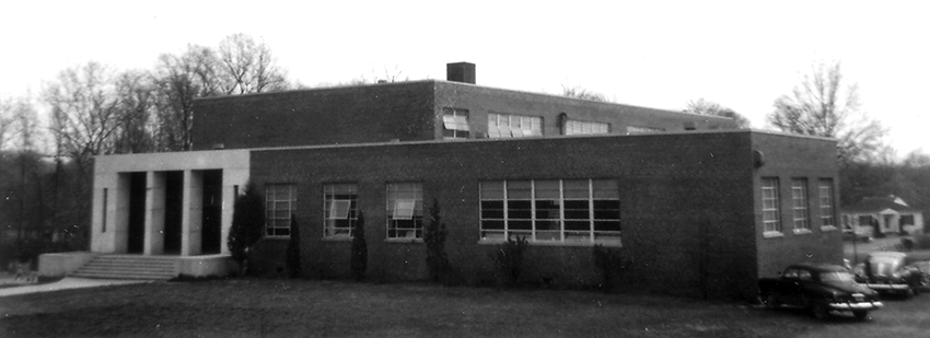 Black and white photograph of Oak Street Elementary School taken in 1954 for the Fairfax County School Board's fire insurance survey of school properties. The building has two stories in an 'L' shape. The main entrance is made of white stone and visually looks very different from the brick exterior. A pair of 1950s era cars are visible on the right side of the image.