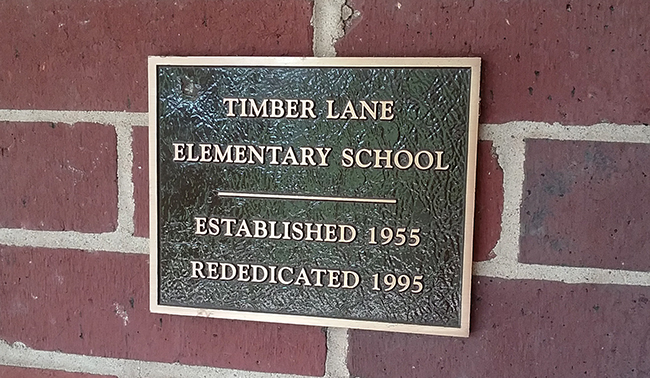 Photograph of the rededication plaque attached to the brick wall at the main entrance to our school. It reads Timber Lane Elementary School, Established 1955, Rededicated 1995.